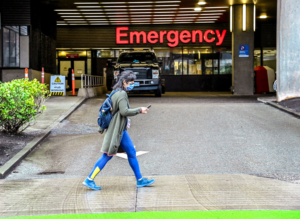 Masked person walks by hospital