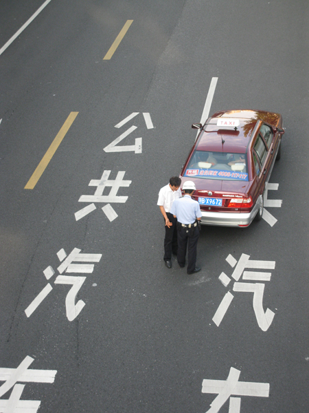 A taxi driver being ticketed in Shanghai