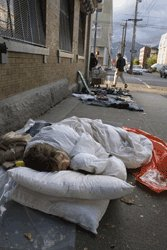 Homeless person sleeping on street with pillows
