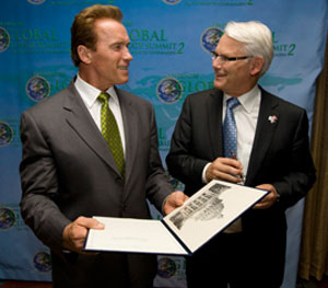 Gordon Campbell hands with shakes Arnold Schwarzenegger
